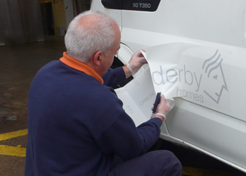 Applying vinyl lettering and logo to a Derby Homes fleet vehivle